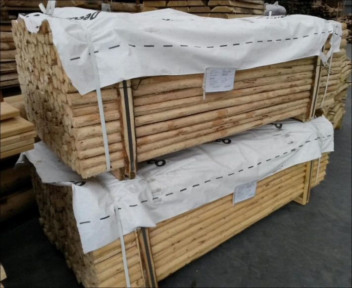 Paller med afbarkede pæle til at lave raftehegn af